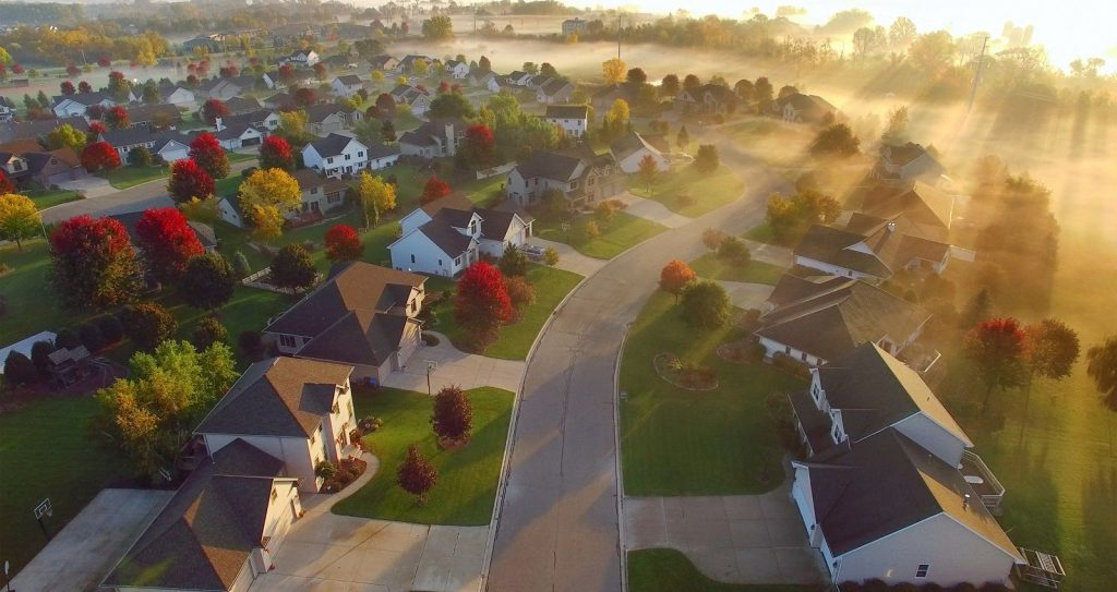 Idyllic Autumn neighborhood shrouded in fog at dawn